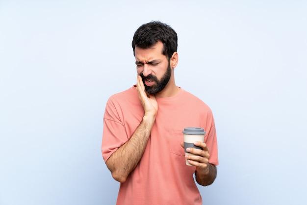 Junger mann mit dem bart, der einen mitnehmerkaffee über lokalisierter blauer wand mit zahnschmerzen hält