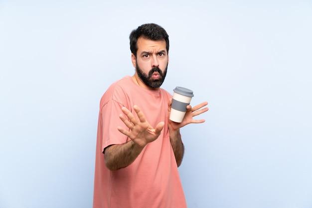 Junger mann mit dem bart, der einen mitnehmerkaffee über lokalisierter blauer wand nervös hält, hände zur front ausdehnend