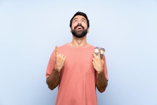 Junger mann mit dem bart, der einen mitnehmerkaffee über lokalisierter blauer wand überrascht hält und oben zeigt