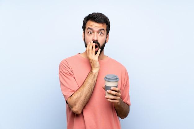Junger mann mit dem bart, der einen mitnehmerkaffee über lokalisierter blauer wand überrascht und beim schauen entsetzt hält
