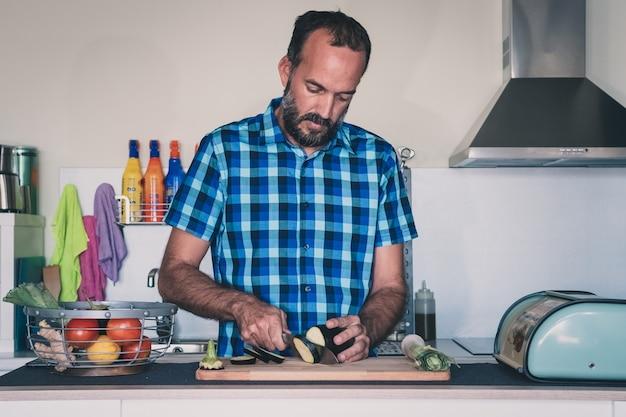 Junger mann mit dem bart, der organische auberginen in seiner dachbodenküche schneidet
