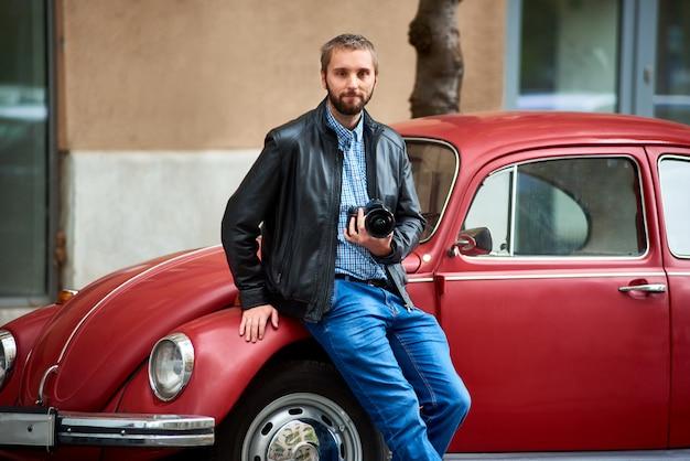 Junger mann mit dem bart, der sich auf rotes retro-auto stützt und in der hand eine professionelle kamera hält