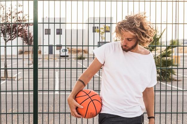 Junger mann mit dem basketball, der gegen zaun steht
