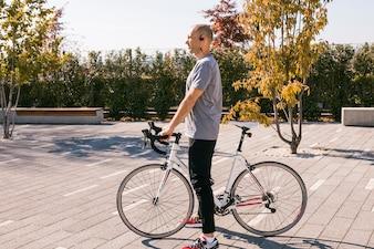 Junger Mann mit dem drahtlosen Bluetooth, das mit weißem Fahrrad im Park steht