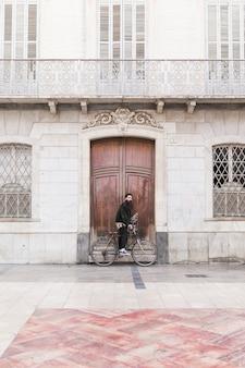 Junger mann mit dem fahrrad, das vor weinlesegebäude steht