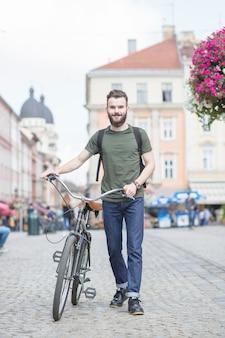 Junger Mann mit dem Fahrrad gehend auf Straße