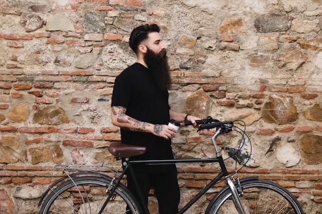 Junger mann mit dem fahrrad, welches die wegwerfkaffeetasse in der hand steht nahe der verwitterten wand hält