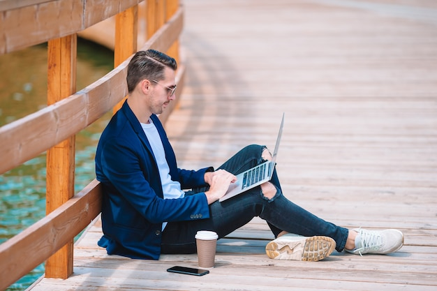 Junger mann mit dem laptop, der draußen im park arbeitet
