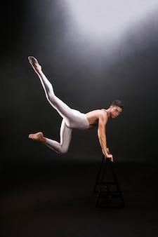 Junger mann mit dem nackten torso, der auf hölzernem stand beim betrachten der kamera springt und sich lehnt