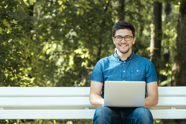 Junger mann mit dem notizbuch, das im park sitzt