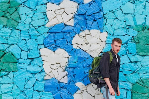 Junger mann mit dem reiserucksack, der nahe gemalter steinwand steht