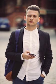 Junger mann mit dem rucksack, der ein telefon hält