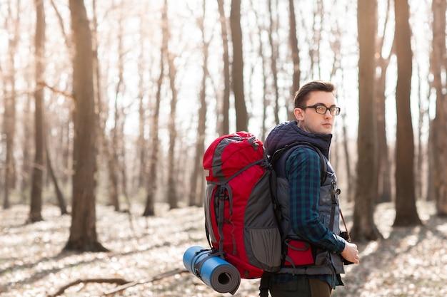 Junger mann mit dem rucksack, der im wald wandert