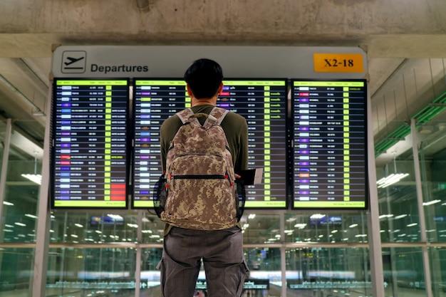 Junger mann mit dem rucksack, der undeutlichen fluginformationsbildschirm am flughafen betrachtet