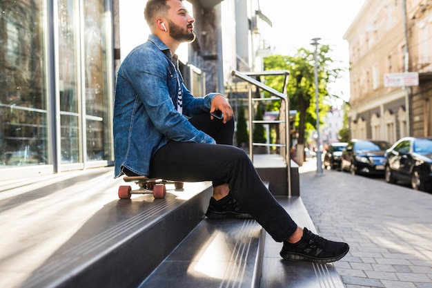 Junger mann mit dem skateboard, das auf treppenhaus sitzt