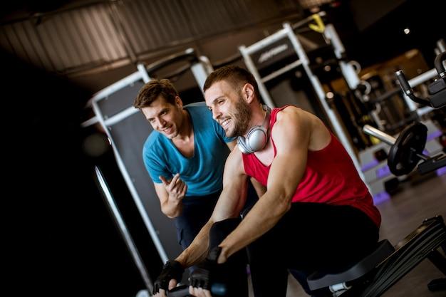 Junger mann mit dem trainer, der übung in der turnhalle tut
