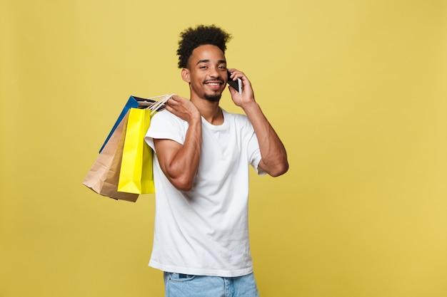 Junger mann mit den einkaufstaschen, die am intelligenten telefon lokalisiert auf gelbem hintergrund sprechen