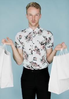Junger mann mit den einkaufstaschen, die zur kamera schauen