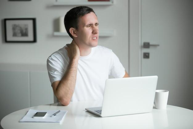 Junger mann mit den händen am hals, sitzt am schreibtisch