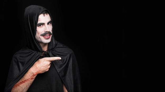 Junger mann mit den künstlichen kratzern, die im halloween-kostüm aufwerfen