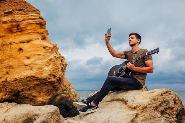 Junger mann mit der akustikgitarre, die selfie unter verwendung des telefons auf bewölktem strand nimmt