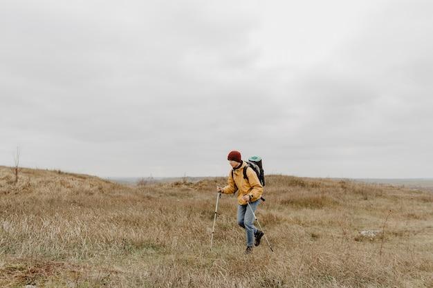 Junger mann mit der ausrüstung, die natur erforscht