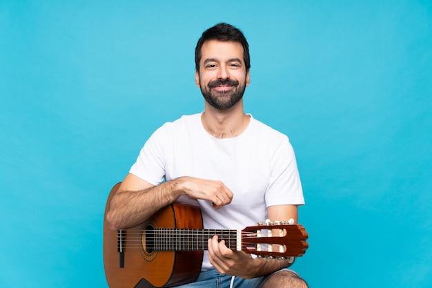 Junger mann mit der gitarre, welche die arme gekreuzt in frontaler position hält
