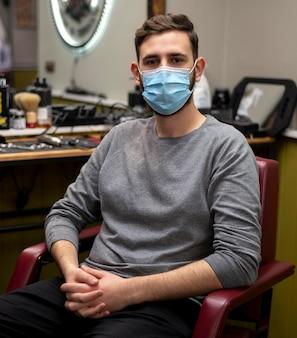 Junger mann mit der medizinischen maske, die am friseurladen wartet