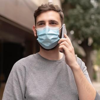 Junger mann mit der medizinischen maske, die beim telefonieren geht