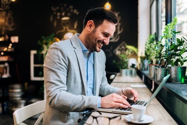 Junger mann mit der verbundenen hand, die front einer laptop-computers im café sitzt.
