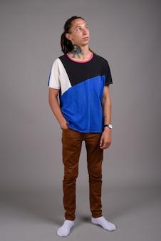 Junger mann mit dreadlocks gegen grauen hintergrund