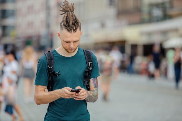 Junger mann mit dreadlocks geht mit einem telefon auf der straße