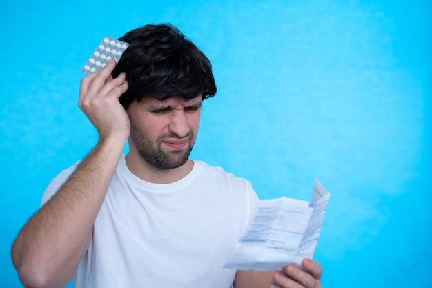 Junger mann mit drogen und pillen kranker mann, der die erklärung der medizin vor der einnahme von verschreibungspflichtigen medikamenten betrachtet