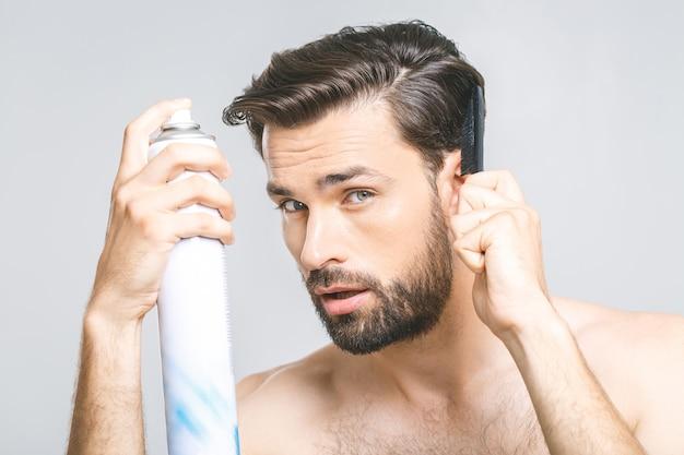 Junger mann mit einem bart auf einem grauen isolierten hintergrund schnurrt ein haarspray. schönheitskonzept.