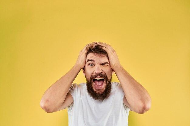 Junger mann mit einem bart in einem t-shirt zeigt verschiedene emotionen, spaß, traurigkeit, wut im studio im hintergrund