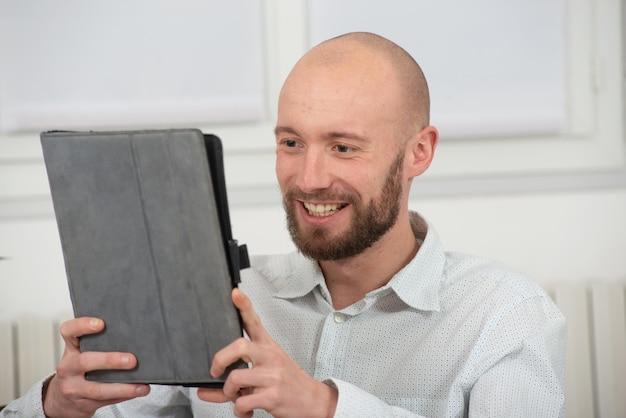Junger mann mit einem bart unter verwendung einer digitalen tablette