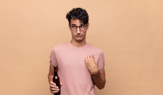 Junger mann mit einem bier, das arrogant, erfolgreich, positiv und stolz aussieht und auf sich selbst zeigt
