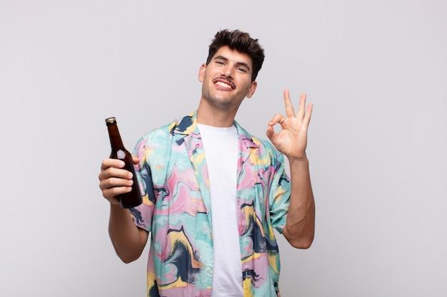 Junger mann mit einem bier, das glücklich, entspannt und zufrieden fühlt, zustimmung mit okay geste zeigt, lächelnd