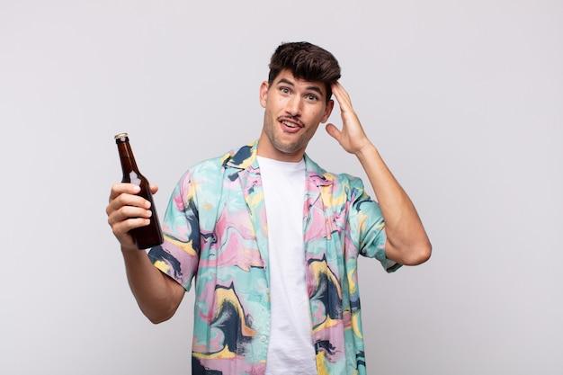 Junger mann mit einem bier, das glücklich, erstaunt und überrascht aussieht, lächelt und erstaunliche und unglaublich gute nachrichten realisiert
