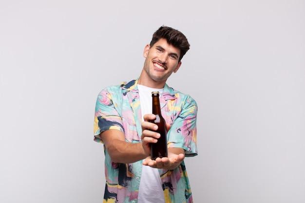 Junger mann mit einem bier, das glücklich mit freundlichem, selbstbewusstem, positivem blick lächelt und ein objekt oder konzept anbietet und zeigt Premium Fotos