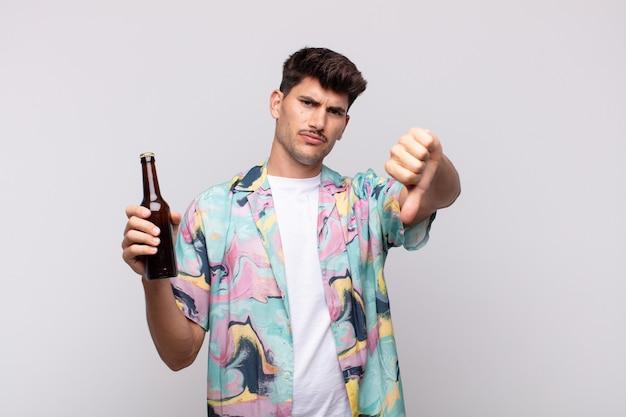 Junger mann mit einem bier, das sich böse, wütend, verärgert, enttäuscht oder unzufrieden fühlt und mit ernstem blick die daumen nach unten zeigt