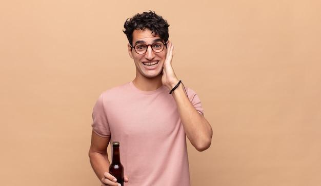 Junger mann mit einem bier, das sich glücklich, aufgeregt und überrascht fühlt und mit beiden händen im gesicht zur seite schaut
