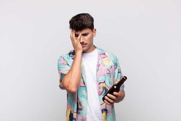 Junger mann mit einem bier, das sich nach einer lästigen, langweiligen und mühsamen aufgabe gelangweilt, frustriert und schläfrig fühlt und das gesicht mit der hand hält