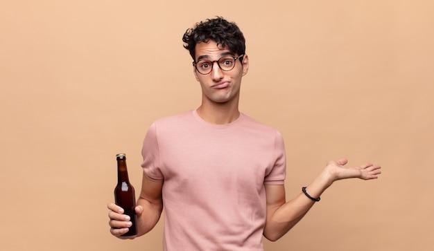 Junger mann mit einem bier, das sich verwirrt und verwirrt fühlt, zweifelt, gewichtet oder verschiedene optionen mit lustigem ausdruck wählt