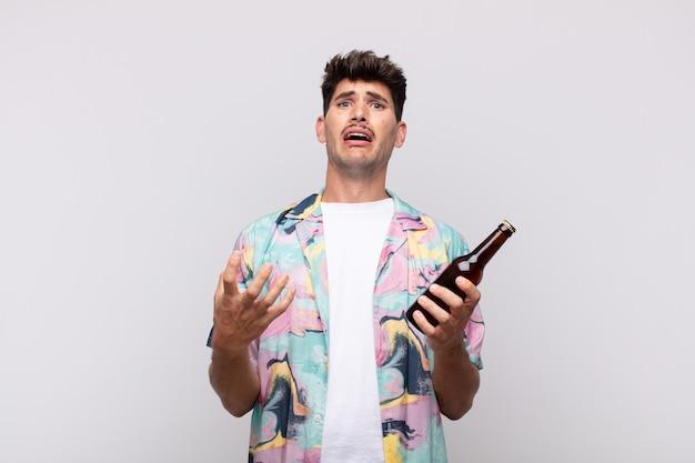 Junger mann mit einem bier, das verzweifelt und frustriert aussieht, gestresst, unglücklich und genervt, schreiend und schreiend