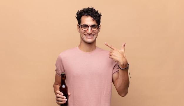 Junger mann mit einem bier, das zuversichtlich lächelt und auf sein eigenes breites lächeln zeigt, positive, entspannte, zufriedene haltung