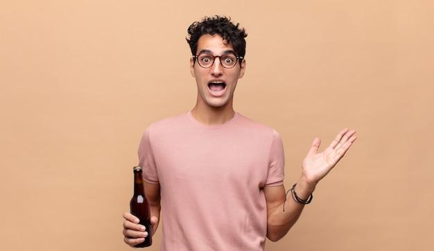 Junger mann mit einem bier, der sich glücklich, aufgeregt, überrascht oder geschockt fühlt, lächelt und erstaunt über etwas unglaubliches