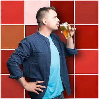 Junger mann mit einem blauen outfit tragen. bier trinken.
