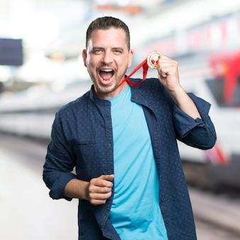 Junger mann mit einem blauen outfit tragen. mit einer goldmedaille.