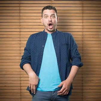 Junger mann mit einem blauen outfit tragen. schauen überrascht.